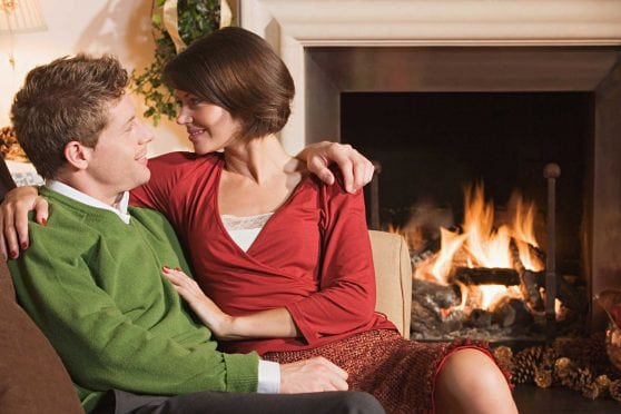 Couple on chair in front of fireplace.