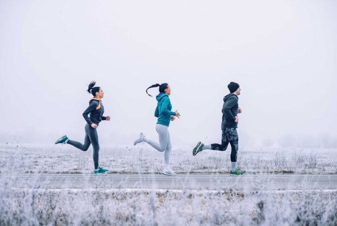 Three people jogging on road, winter background.