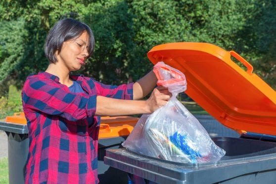 Woman taking out trash.
