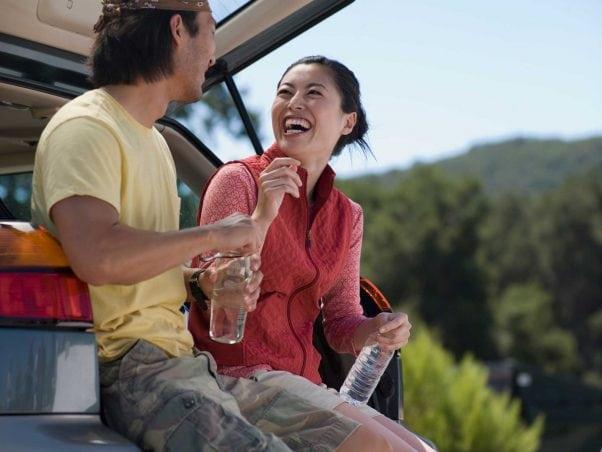 Couple sitting on back of SUV.