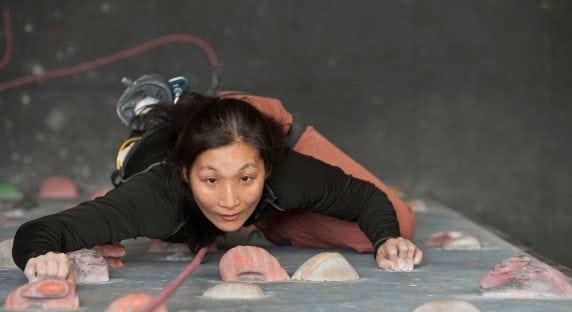 Woman at indoor rock-climbing facility.