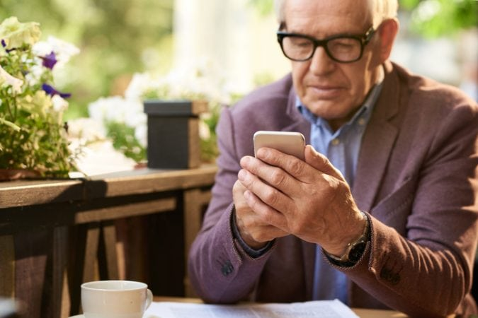 Senior Man Holding Smartphone in Cafe