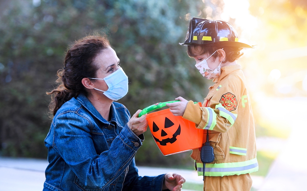 Mature woman and a child boy wearing protective face masks before going to ask trick or treat halloween