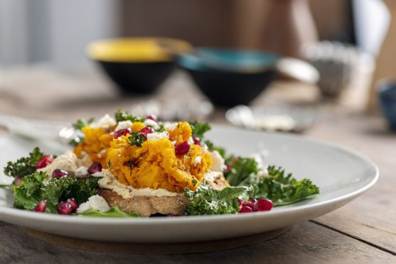 Butternut squash with kale,feta cheese,hummus and pomegranate on toast.