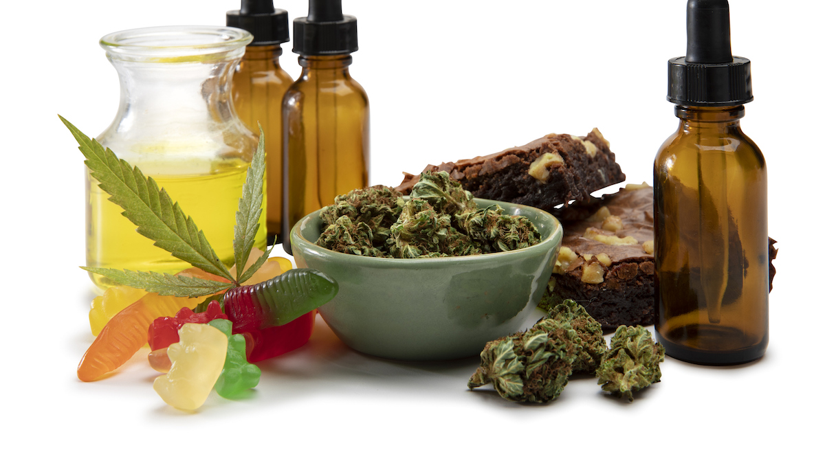 Cannabis oils and bud in a small bowl surrounded by sweet edibles